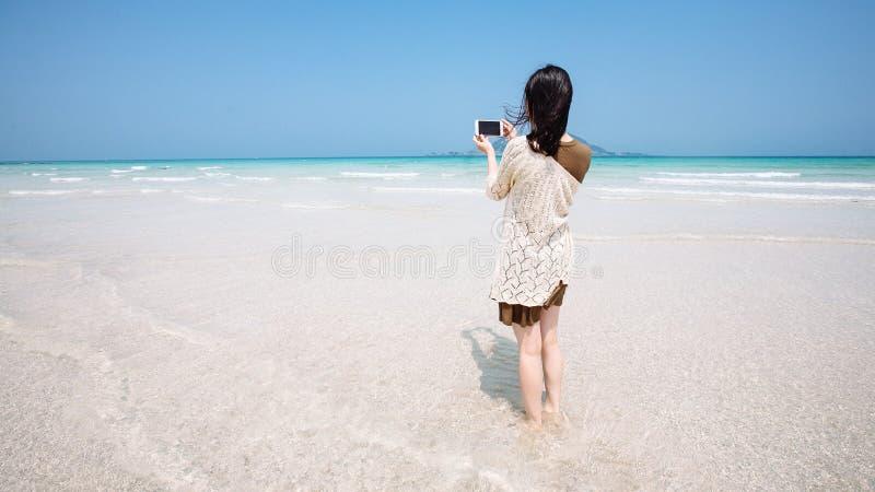 Un voyageur féminin prend la photo de l'océan de turquoise avec une île de Jeju de caméra de téléphone portable image stock