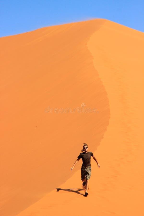 Un voyageur masculin dans des courses de vêtements de sport à travers le sable orange d'une dune en parc national de Soussefly image libre de droits
