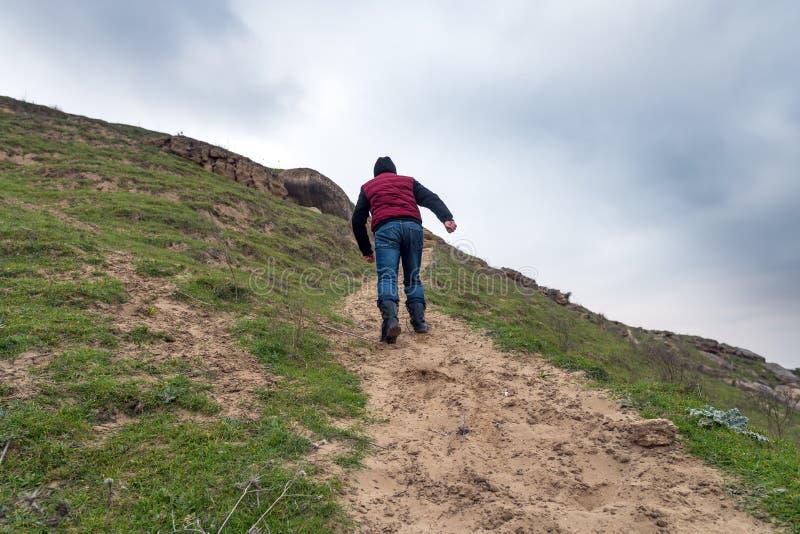 Un voyageur solitaire monte une crête de montagne images libres de droits