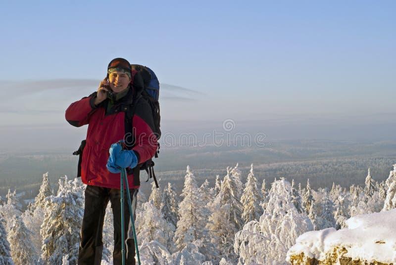 Un voyageur sur une montagne parlant sur un smartphone photographie stock