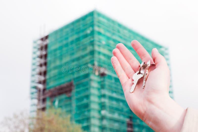 Un vrai agent immobilier tenant des clés sur un nouvel appartement dans des ses mains. photographie stock