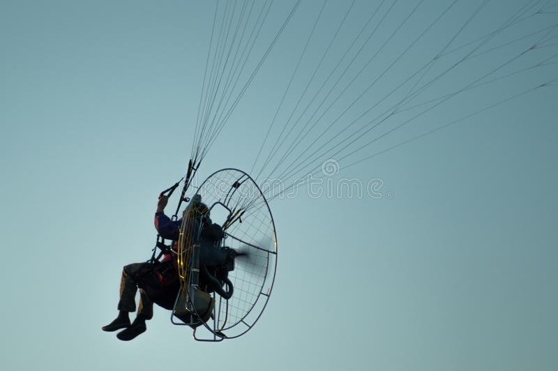 Un vuelo del hombre en el cielo en un ala flexible Silueta de un paragli imagenes de archivo