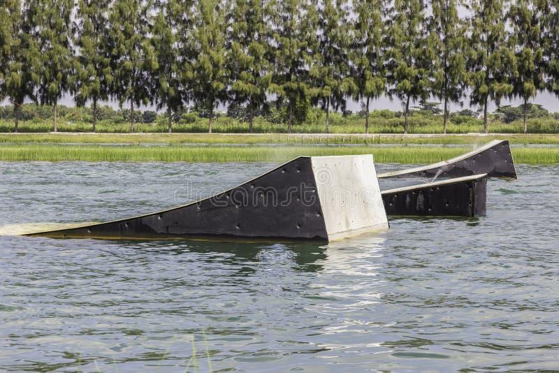 Un wakeskater glisse à travers un obstacle de flottement énorme de rail derrière photo stock