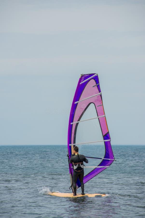 Un windsurfer monta en el mar en calma, viento ligero La visi?n desde la parte posterior imagen de archivo libre de regalías