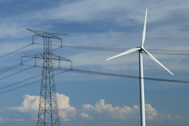 Un windturbine cerca de un pilón eléctrico imágenes de archivo libres de regalías
