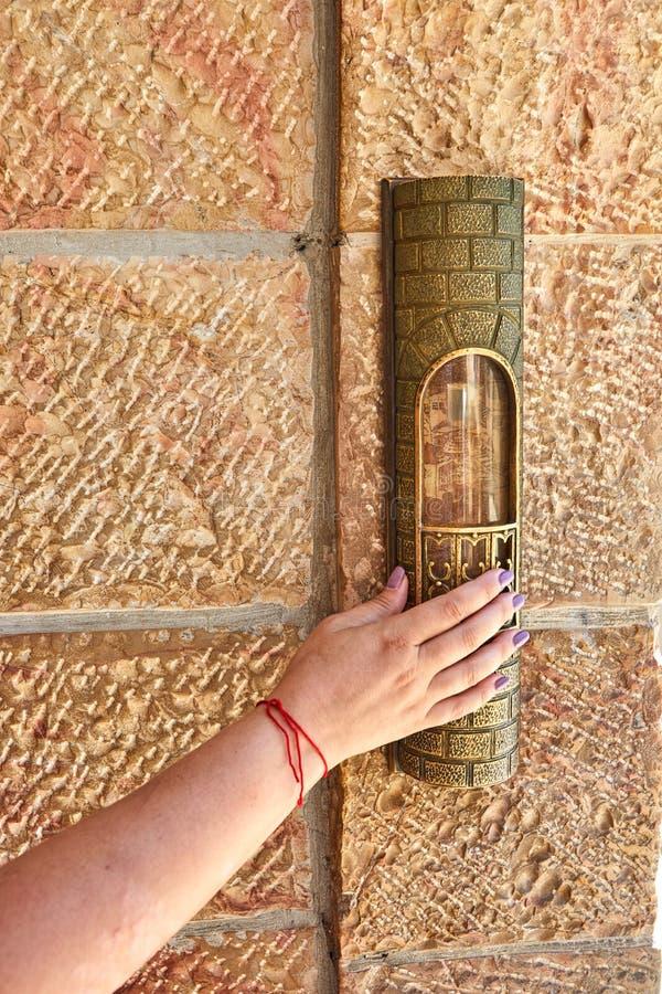 Un woman& x27; la mano de s con un hilo rojo toca el mezuzah en la entrada al área cerca foto de archivo