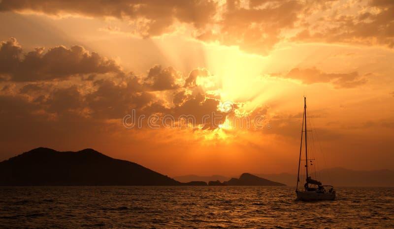 Un yacht à la mer pendant un coucher du soleil photographie stock