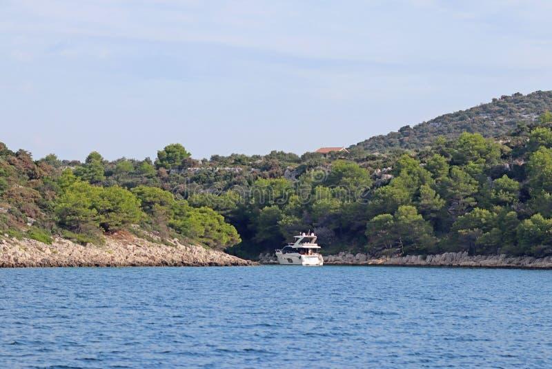 Un yate de lujo del motor ocultó en la ensenada de la isla de Dalmacia en Croacia Resto activo en el mar adriático de la región m fotografía de archivo