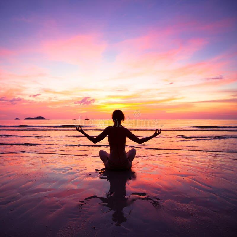 Un yoga de pratique de femme se reposant sur la plage images stock