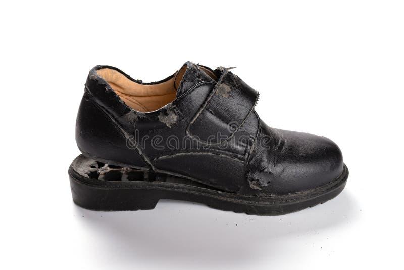 Un zapato de cuero gravemente quebrado en blanco foto de archivo