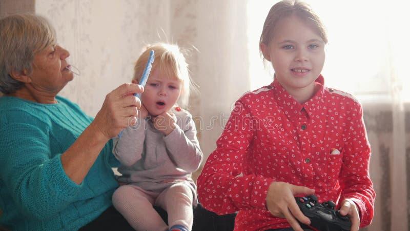 Una abuela que peina el pelo de su nieta Otra muchacha que juega con la palanca de mando imagen de archivo