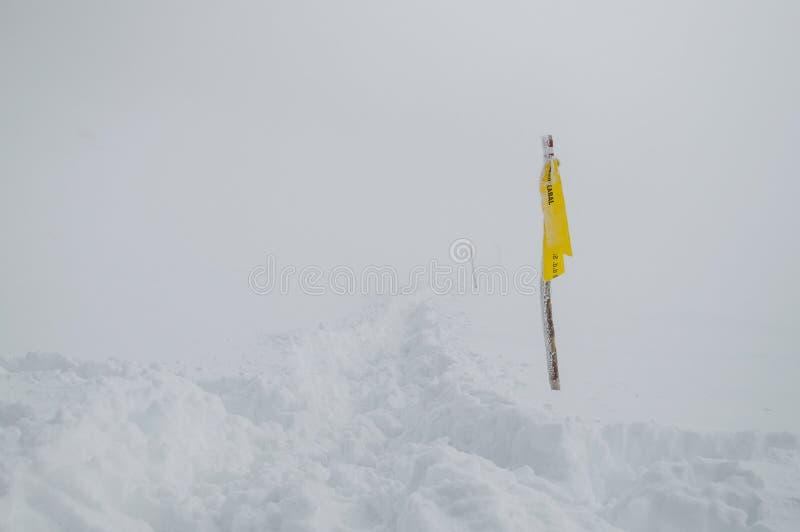 Una advertencia amarilla en un rastro de montaña nevoso y de niebla imagen de archivo