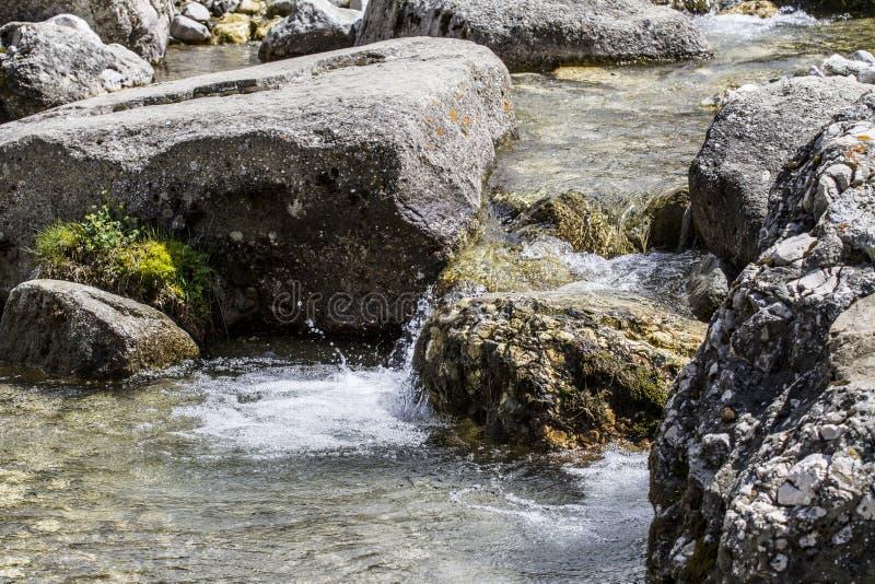Una agua pequeña, pura, clara y fría que fluye de las montañas de mi patria foto de archivo libre de regalías