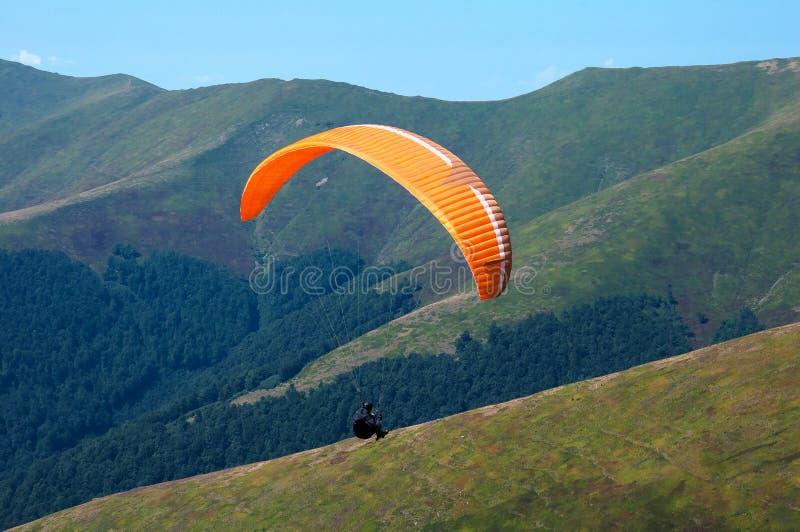Una ala flexible vuela sobre un valle de la montaña en día soleado del verano en los Cárpatos en Ucrania imágenes de archivo libres de regalías