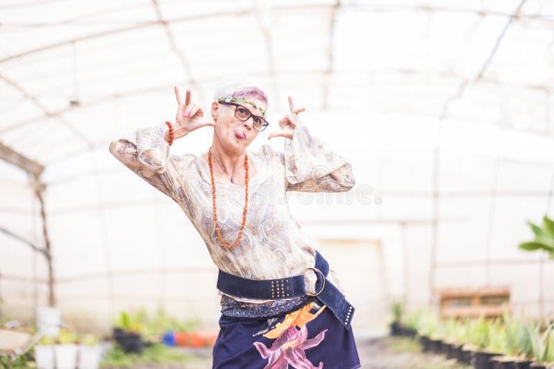 Una alegre mujer blanca de cabello alto sonríe y posar para un retrato hippy - felicidad y estilo de vida colorido para imagen de archivo