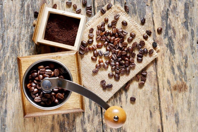 Una amoladora de café y granos de café foto de archivo
