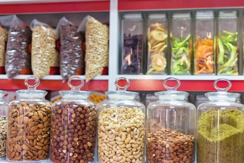 Una amplia variedad de nueces y de frutas secadas en los bancos de cristal en los estantes imagenes de archivo