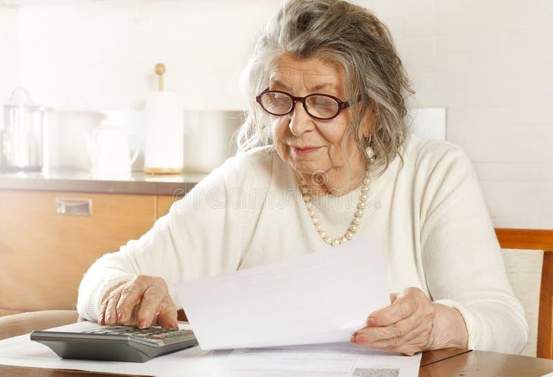 Una anciana que busca recibos con una calculadora foto de archivo