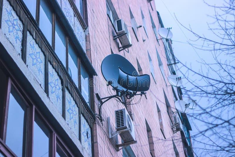 Una antena parabólica en una pared de ladrillo foto de archivo libre de regalías
