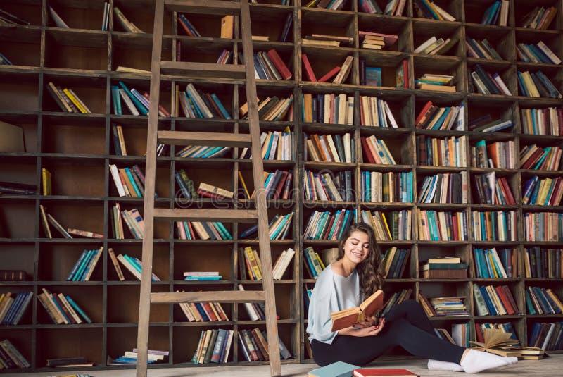 Una atmósfera de la lectura apasionada de la historia mujer joven preciosa de los libros de lectura Sitio acogedor de la bibliote fotos de archivo