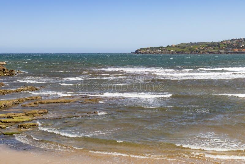 Una baia pittoresca dell'oceano con una spiaggia sabbiosa e una città sulla montagna nei precedenti fotografie stock libere da diritti