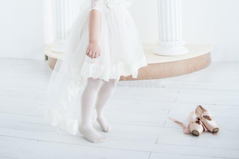 Una ballerina della bambina salta senza scarpe ed accanto lei è scarpe del pointe immagini stock libere da diritti