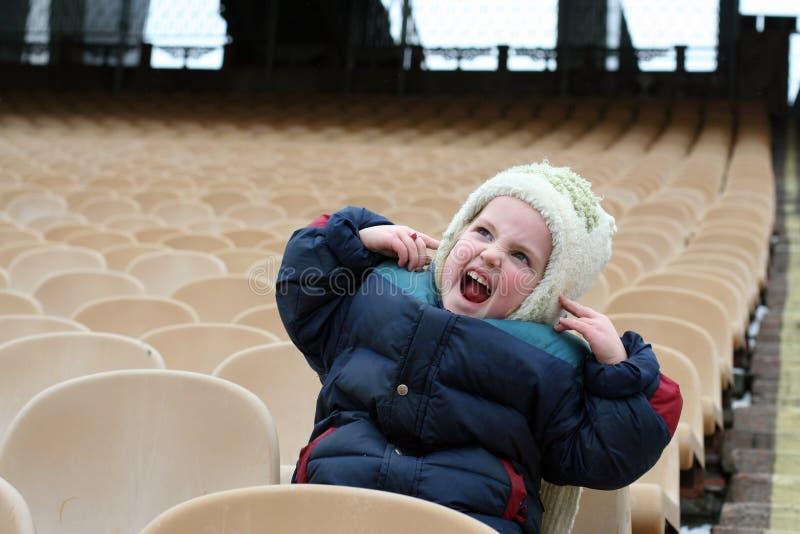 Una bambina è sulla zona vuota per i fan nello stadio e fa gli smorfie immagini stock libere da diritti