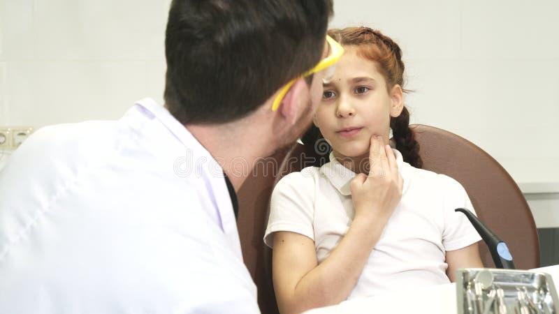 Una bambina è venuto al dentista e si lamenta di un dolore in un dente fotografia stock
