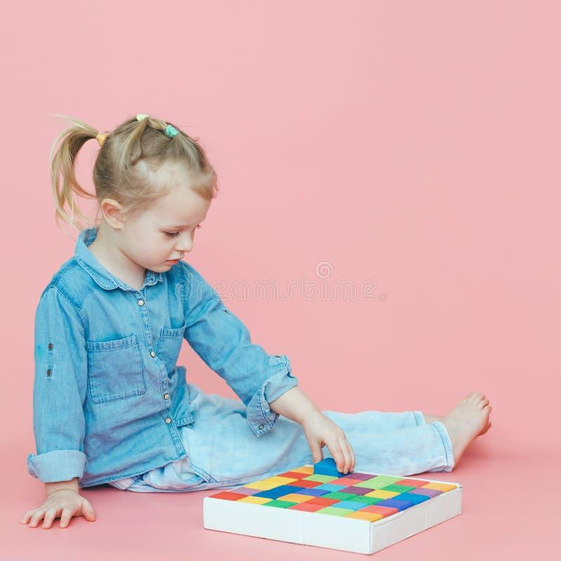 Una bambina affascinante in vestiti del denim su un fondo rosa mette dei i cubi colorati multi di legno in una scatola bianca fotografia stock