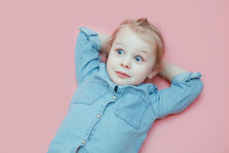 Una bambina bianca sveglia sta trovandosi su un fondo rosa con le sue mani dietro la sua testa immagine stock