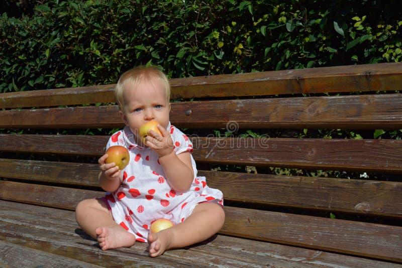 Una bambina bionda mangia due mele immagini stock