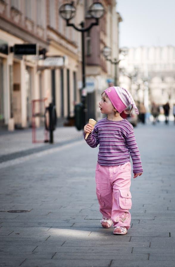 Una bambina che cammina lungo la via con un ghiaccio-creame immagini stock