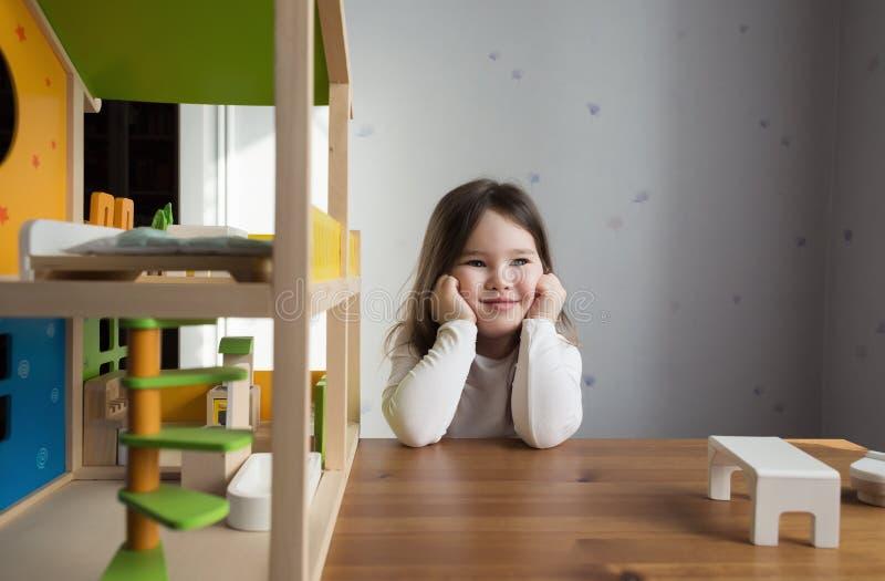 Una bambina che gioca con la casa delle bambole immagini stock libere da diritti