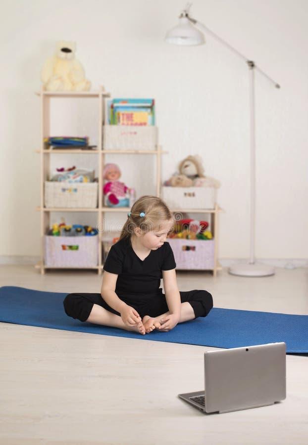 Una bambina che guarda video online sul portatile e fa allenamenti o esercizi di fitness nella sua stanza a casa Distante immagine stock libera da diritti