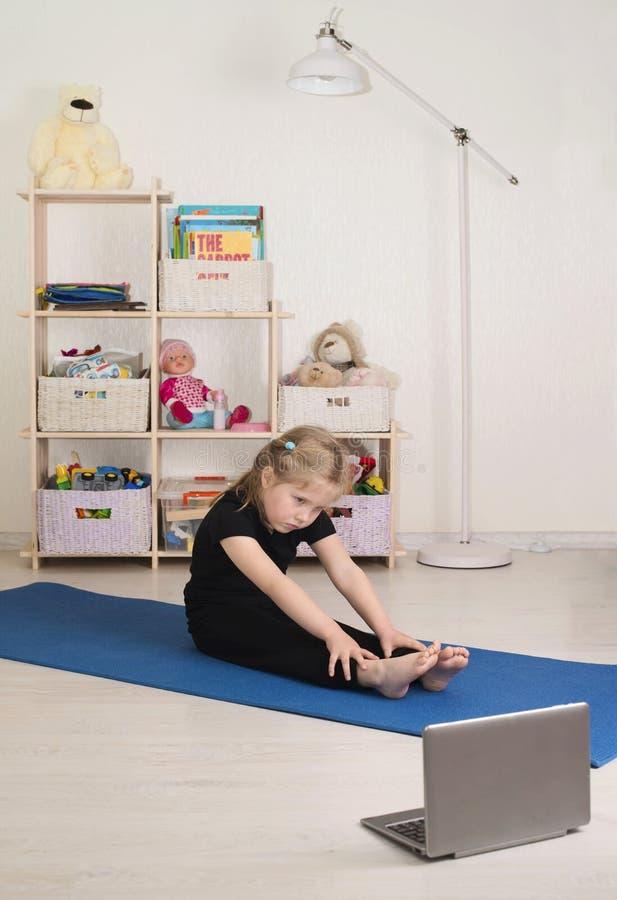 Una bambina che guarda video online sul portatile e fa allenamenti o esercizi di fitness nella sua stanza a casa Distante fotografia stock