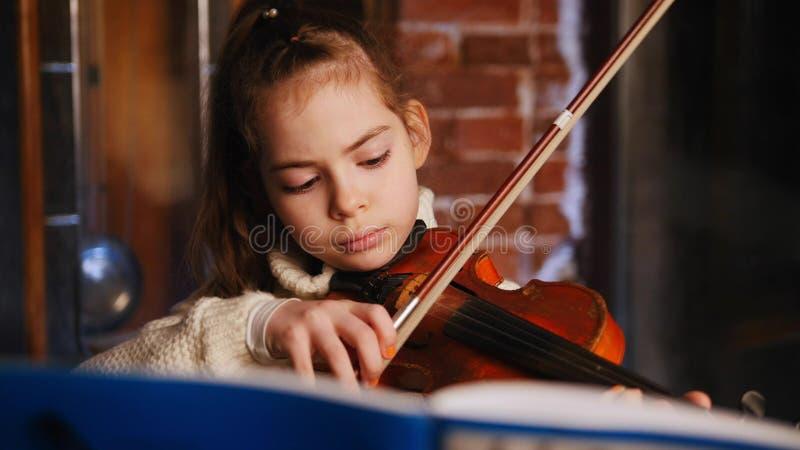 Una bambina che impara una composizione dalle note Gioco del violino fotografia stock