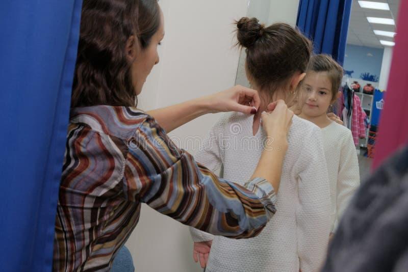 Una bambina che prova su un vestito dal bambino con sua madre nello spogliatoio Acquisto con i bambini La mamma compra le cose pe fotografie stock libere da diritti