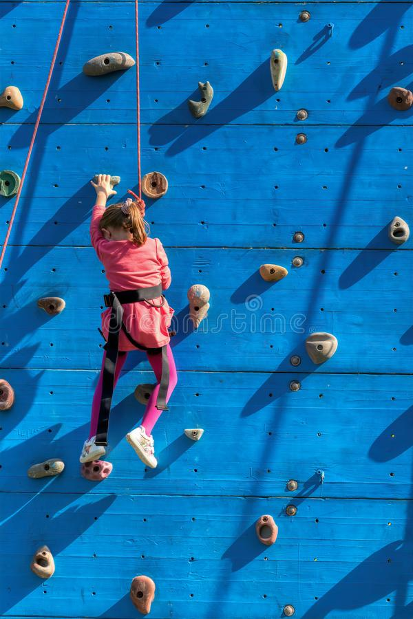 Una bambina che scala su una parete verticale fotografie stock libere da diritti