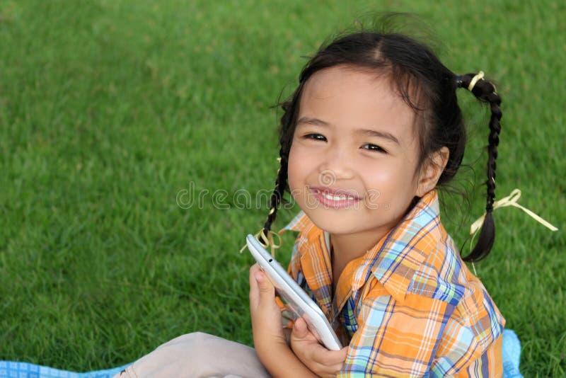 Una bambina che si siede nel parco fotografia stock