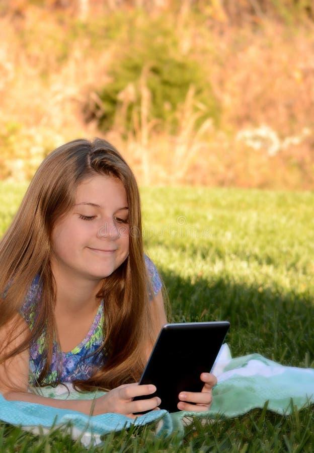 Una bambina che si trova sull'erba con la sua compressa immagini stock