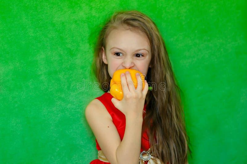 Una bambina che tiene un pepe giallo dolce in sua mano fotografia stock