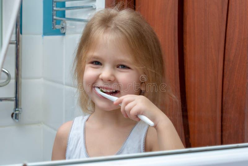 Una bambina con capelli biondi che puliscono i suoi denti Il bambino sta sorridendo alla riflessione nello specchio immagini stock
