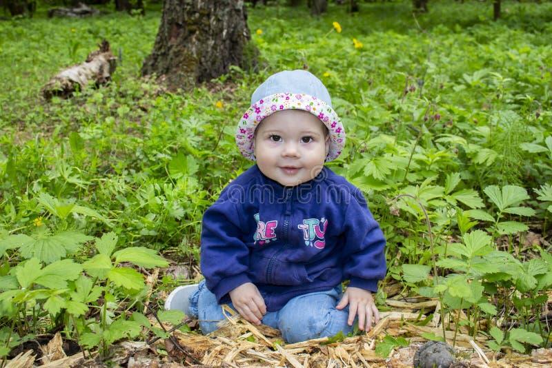 Una bambina con il maglione ed il cappello si siede in mezzo alla foresta e esamina la macchina fotografica Una ragazza felice im fotografie stock libere da diritti