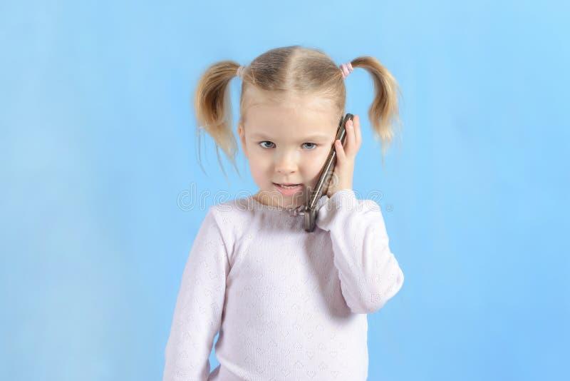 Una bambina con le code dei capelli due Bambino sveglio con capelli biondi che parla su uno smartphone fotografie stock libere da diritti