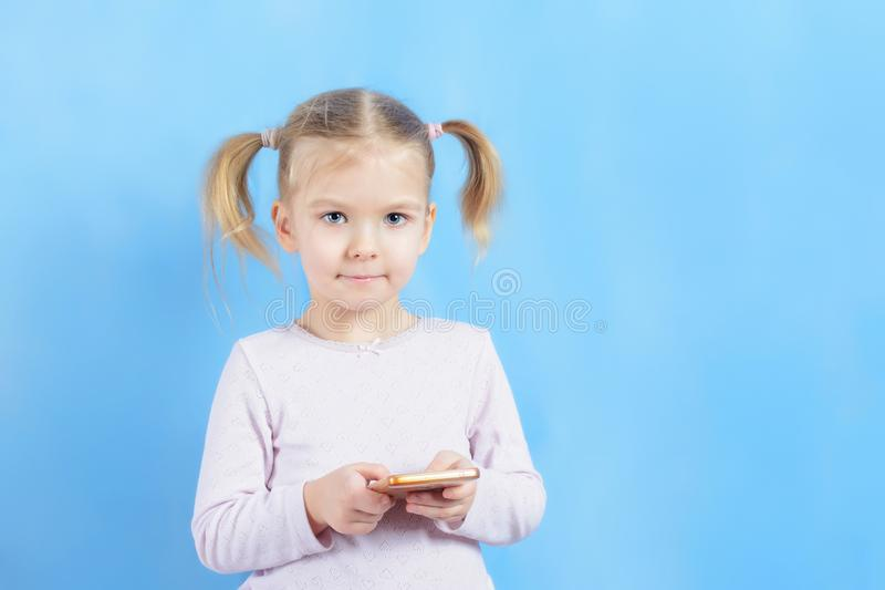 Una bambina con le code dei capelli due Bambino sveglio con capelli biondi che tengono uno smartphone fotografia stock
