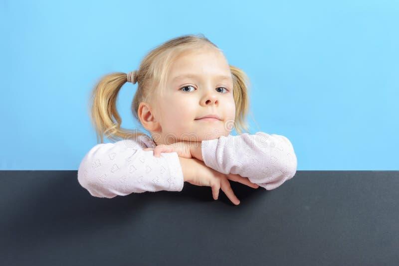 Una bambina con le code dei capelli due Bambino sveglio con capelli biondi Fondo su uno strato nero del cartone, un posto per tes fotografie stock libere da diritti