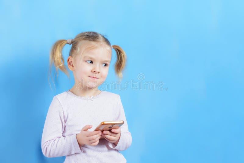 Una bambina con le code dei capelli due Il bambino sveglio con capelli biondi, qualcosa sta scrivendo sullo smartphone immagine stock