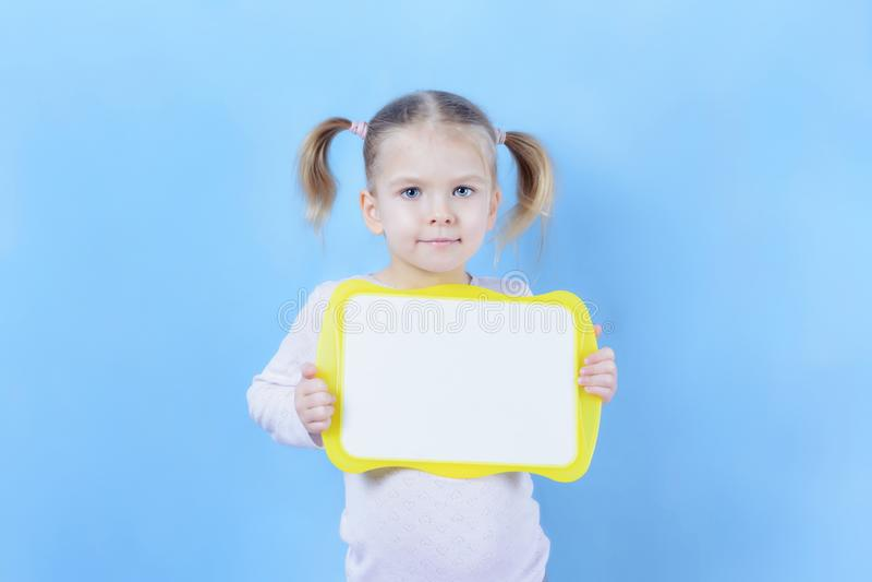 Una bambina con le code dei capelli due Un bambino sveglio con capelli biondi sta tenendo un segno con spazio per testo fotografia stock libera da diritti