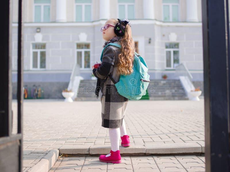 Una bambina con le code rosse davanti alla scuola, distogliente lo sguardo fotografia stock libera da diritti