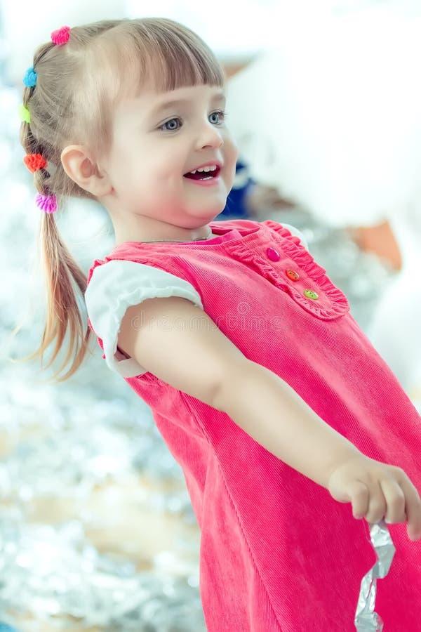 Una bambina con le risate delle trecce e divertiresi ad un partito dei bambini fotografia stock